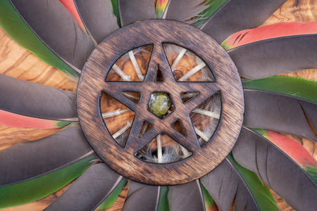 Wooden encircled Pentagram symbol with Unakite stone in the middle of a circle made of colorful parrot feathers. Five elements: Earth, Water, Air, Fire, Spirit. Stockfoto