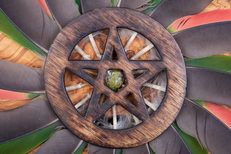 Wooden encircled Pentagram symbol with Unakite stone in the middle of a circle made of colorful parrot feathers. Five elements: Earth, Water, Air, Fire, Spirit. 免版税图像