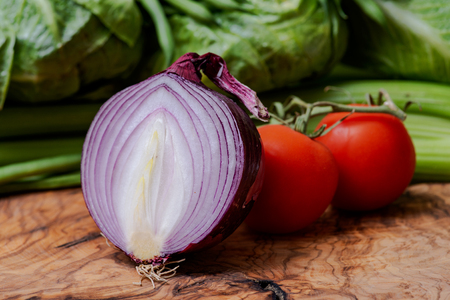 Red Onion cut in half and Organic Red Tomatoes on the vine arranged on natural olive wood. Stock Photo