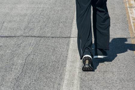 Legs of a runner jogging on asphalt road in sport shoes.