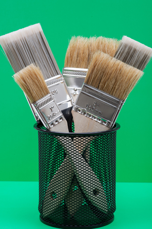 Flat Chip and Flat Cut Utility Paint Brushes on green background.