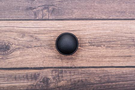 Manopola rotonda nera classica dell'armadietto isolata su fondo di legno.