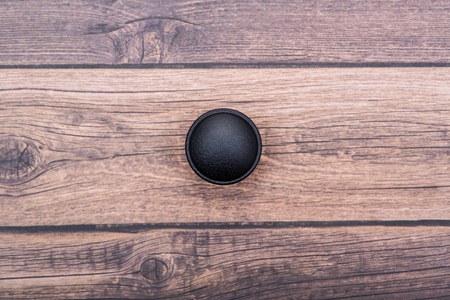 Perilla de gabinete redonda negra clásica aislada sobre fondo de madera.