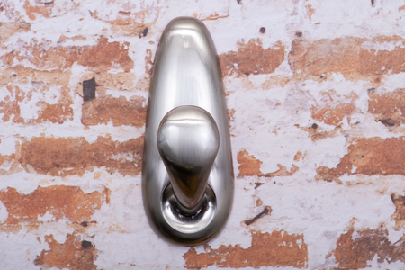 Brushed Nickel Metal Wall  Hook with Damage-Free Hanging isolated on brick  wall background.
