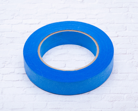 Blue Painter's Tape for multi surfaces isolated on white brick wall background. Banco de Imagens