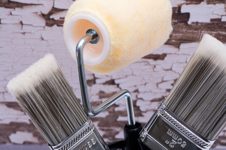 Flat Cut Utility Paint Brushes and High Density Knit Fabric Trim Roller with Frame  on wooden background.