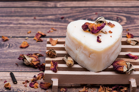 Wooden Soap Holder with a Heart shaped Goat milk Soap and dried roses on wooden background.