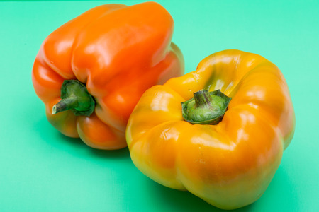 Fresh Ripe Organic Bell Peppers, a cultivar group of the species Capsicum annuum, isolated on green background.