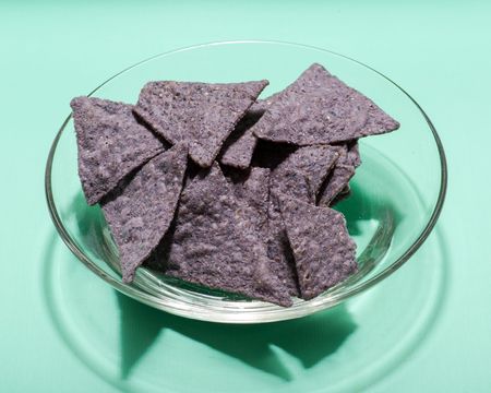 Lightly Salted Organic Blue Corn Tortilla Chips in clear glass bowl isolated on green background.