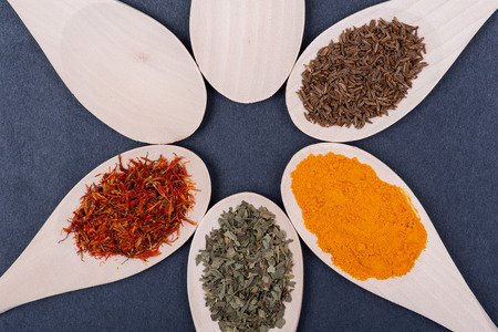 Collection of spices in wooden spoons (Saffron, Basil, Turmeric, Caraway Seeds) on dark background. Standard-Bild