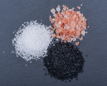 Piles of Hawaiian Black Lava Sea Salt, Coarse White Sea Salt and Himalayan Pink Salt on dark background.