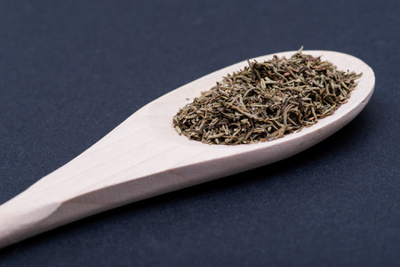 Heap of Dried Organic Culinary Thyme Herb in handmade wooden spoon on dark background. Thymus vulgaris.
