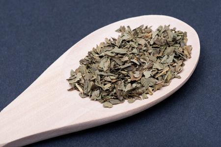 Dried natural Basil spice (Ocimum basilicum) in handmade wooden spoon on dark background. Imagens