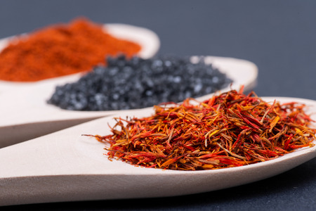 Saffron, Black Lava Sea Salt and Sweet Paprika in wooden spoons on dark background. Standard-Bild