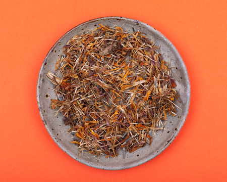 Marigold Dry Seeds (Mexican marigold, Aztec marigold, African marigold) in ceramic plate on orange background. Tagetes erecta. Daisy family. Standard-Bild - 123497691
