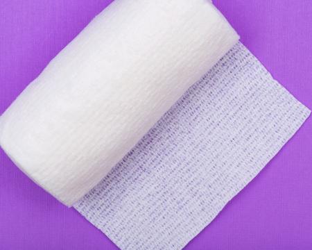 Hospital Grade Sterile Rolled Gauze on purple background.