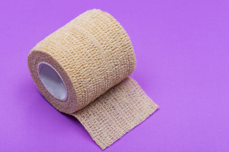 Elastic Self-Adhering Compression Bandage (Cohesive Bandage) on purple background.