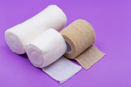Hospital Grade Sterile Rolled Gauze and Elastic Self-Adhering Compression Bandage (Cohesive Bandage) on purple background.