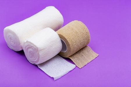 Hospital Grade Sterile Rolled Gauze and Elastic Self-Adhering Compression Bandage (Cohesive Bandage) on purple background.