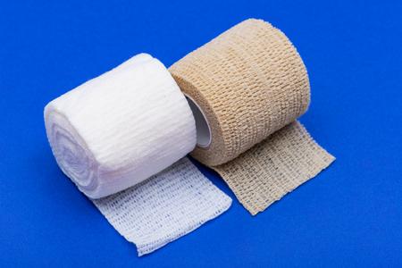 Hospital Grade Sterile Rolled Gauze and Elastic Self-Adhering Compression Bandage (Cohesive Bandage) on blue background.