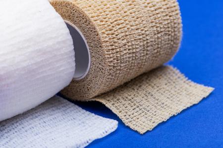 Gaze roulée stérile de qualité hospitalière et bandage de compression élastique auto-adhésif (bandage cohésif) sur fond bleu. Banque d'images
