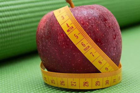 Red Apple and Soft Vinyl Measuring Tape on Green Yoga Mat. Stockfoto