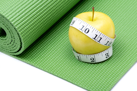 Yellow Apple and Soft Vinyl Measuring Tape on Green Yoga Mat.