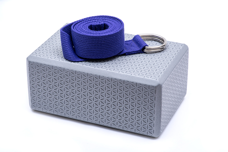 Purple Yoga Strap on Grey Yoga Block isolated on white background. Stockfoto