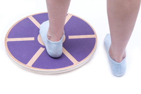 Woman's foot on Wooden Wobble Balance Board Exercise Core Fitness Trainer for Workout, Fitness, Balance Exercise & Rehabilitation. Reklamní fotografie