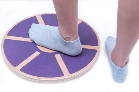 Woman's foot on Wooden Wobble Balance Board Exercise Core Fitness Trainer for Workout, Fitness, Balance Exercise & Rehabilitation. Фото со стока