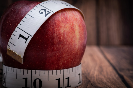 Red Apple and Soft Vinyl Measuring Tape on wooden background. Stockfoto
