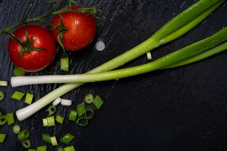 Organic Red Tomatoes on the vine and Green Onion Scallions arranged on black natural stone background. Solanum lycopersicum. Allium onion species.