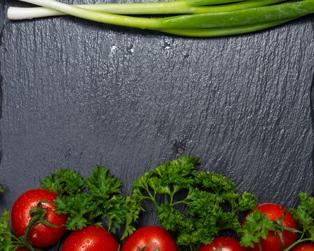 Organic Red Tomatoes on the vine, fresh Curly Parsley and Green Onion Scallions arranged on natural stone background.