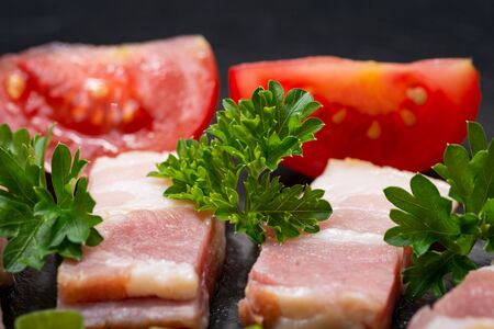 Uncured Apple Smoked Bacon, Red Tomatoes and fresh Curly Parsley arranged on natural black stone background.