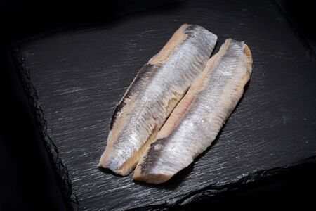Salted boneless fillets of wild-caught Atlantic Herring arranged on natural black stone background. Clupea harengus.