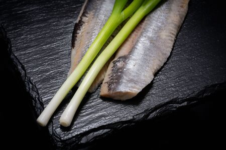 Salt Herring Fillets and Organic Green Onion Scallions arranged on black natural stone background. Clupea harengus. Allium onion species.