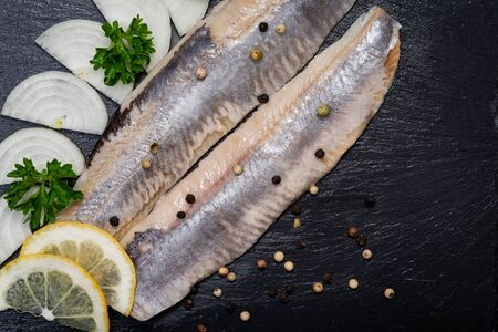 Salted Deboned Herring Fillets garnished with Yellow Onion, Lemon, Fresh Parsley and Peppercorns. Natural black stone background. Clupea harengus.
