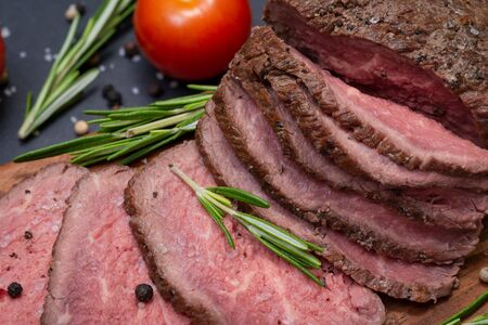 Sliced Grass Fed juicy Corn Roast Beef garnished with Tomatoes, Fresh Rosemary Herb and Rainbow Peppercorns on natural wooden cutting board.