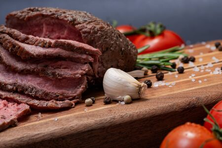 Sliced Grass Fed juicy Corn Roast Beef garnished with Tomatoes, Fresh Rosemary Herb, Garlic and Rainbow Peppercorns on natural wooden cutting board. Stock Photo