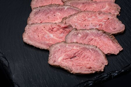 Sliced Grass Fed Juicy Corn Roast Beef on black natural stone background.