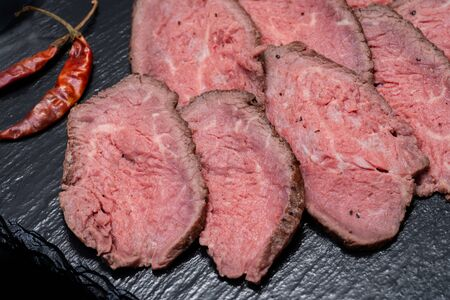 Sliced Grass Fed Juicy Corn Roast Beef garnished with dried Red Chile De Arbol Pepper on black natural stone background.