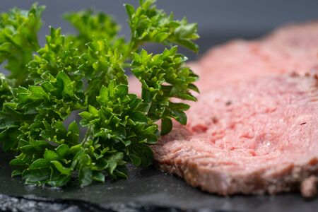 Sliced Grass Fed Juicy Corn Roast Beef garnished with Fresh Curly Parsley on black natural stone background.