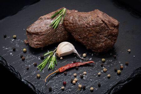 Carne asada de maíz alimentada con pasto adornada con romero fresco, pimiento rojo seco, ajo y granos de pimienta arco iris sobre fondo de piedra negra natural.