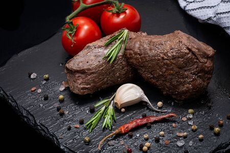 Grass Fed Corn Roast Beef garnished with Tomatoes, Fresh Rosemary, dried Red Chile Pepper, Garlic and Peppercorns on natural black stone background.