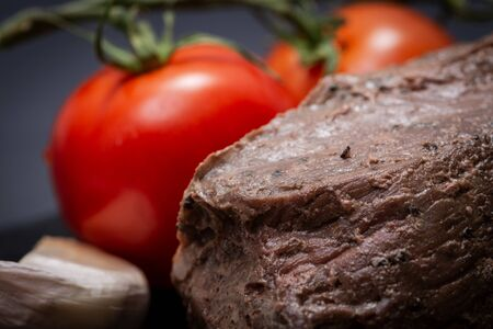 Grass Fed Corn Roast Beef garnished with Tomatoes, Fresh Thyme, dried Red Chile Pepper, Garlic and Peppercorns on natural black stone background. Stock Photo