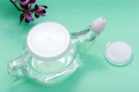 Neti Pot with Soft Comfort Tip, pile of Saline and Purple Orchid Flowers on green background. Sinus wash. Nasal irrigation.