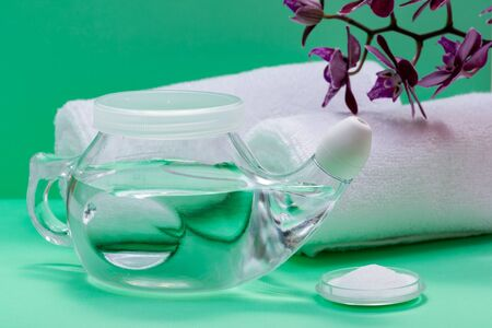 Neti Pot with Soft Comfort Tip, pile of Saline, Purple Orchid Flowers and rolled up White Towels on green background. Sinus wash. Nasal irrigation.