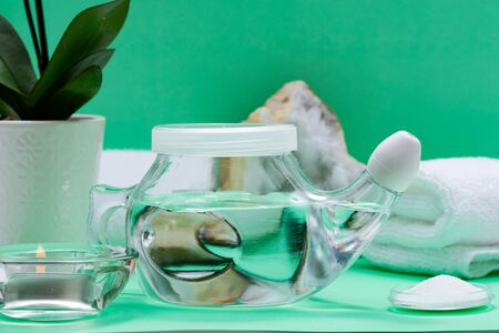 Neti Pot, pile of Saline, rolled White Towels, Purple Orchid Flowers and Lavender Tea Light Candle on green background. Sinus wash. Nasal irrigation.