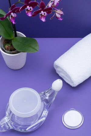 Neti Pot with Soft Comfort Tip, pile of Saline, Purple Orchid Flowers and rolled up White Towels on purple background. Sinus wash. Nasal irrigation.