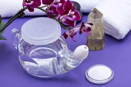 Neti Pot, Saline, Orchid Flowers, rolled up White Towels and Polished Citrine Quartz Point on purple background. Sinus wash. Nasal irrigation.